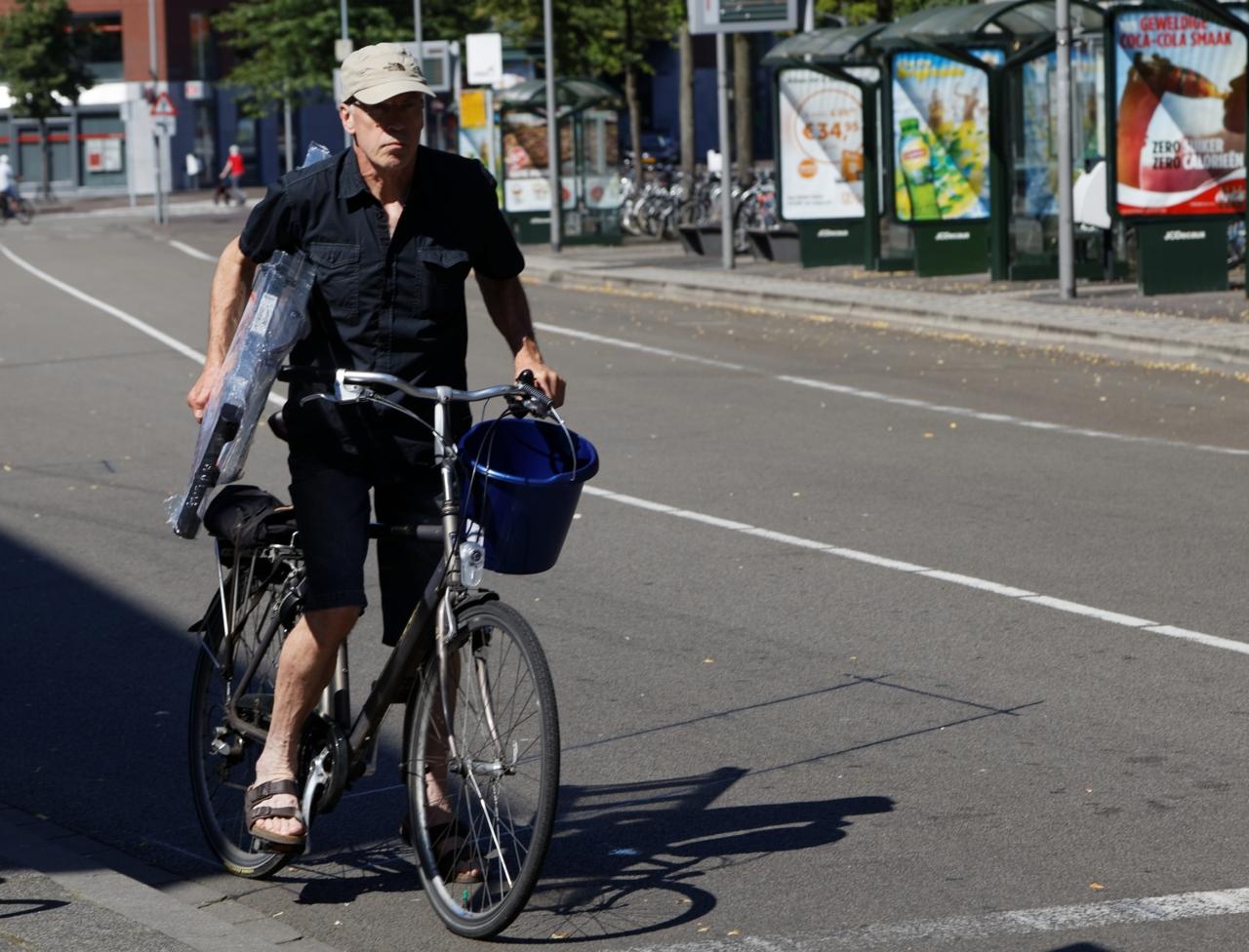 Mann på sykkel med stige